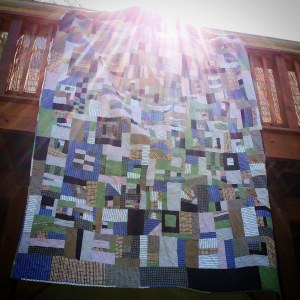 Quilt made from old shirts in a random pattern hung from deck with sunburst